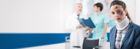 Young female patient with cervical collar support at the hospital and professional doctors on the background, healthcare banner