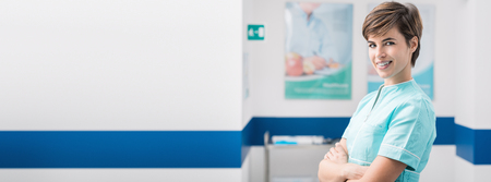 Confident young female nurse posing in the hospital aisle and smiling at camera, healthcare professionals banner Reklamní fotografie
