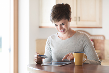 Smiling woman having a coffee break and doing online shopping with her tablet and a credit card