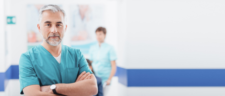 Professional confident doctor posing at the hospital and smiling at camera, a nurse is working on the background Stock Photo