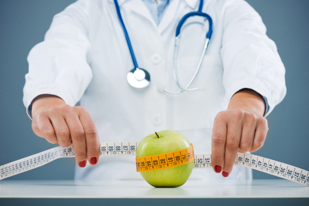 Nutritionist measuring an apple with measuring tape, dieting and weight loss concept