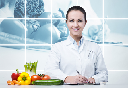 Smiling nutritionist writing medical prescriptions with fresh vegetables