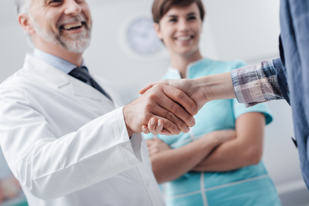 Medical staff welcoming a patient at the clinic: the doctor is giving an handshake and smiling, medical service and healthcare professionals concept, hands close up Banco de Imagens