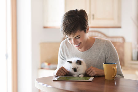 Smiling young woman having a coffee break at home, she is connecting with a tablet and cuddling her kitten