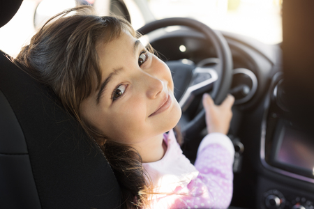 Cute girl sitting on the drivers seat in a car, she is holding the steering wheel and smiling