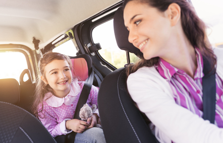 Cute young girl in a car with her mother, they are sitting and smiling at each other