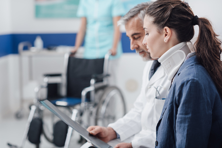 Doctor examining x-ray and medical records of an injured young patient with cervical collar and nurse pushing a wheelchair on the background Stockfoto