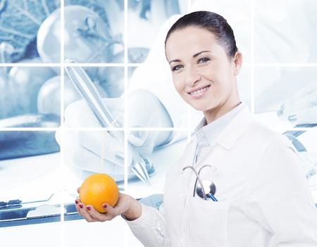 빨대를 사용하여 오렌지에서 직접 오렌지 주스를 마시는 여성 의사 스톡 콘텐츠