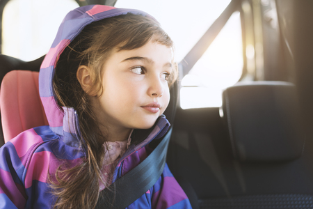 Cute girl sitting in a car and looking out from the car window