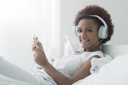 Young african american woman relaxing on the bed and connecting with a touch screen tablet, she is smiling and wearing headphones