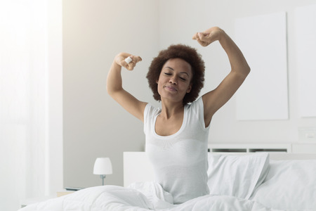 Young african woman waking up early in the morning, she is sitting in her bed and stretching Stock Photo