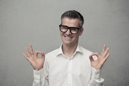 Tevreden gelukkig man met een goed teken en glimlachend in de camera Stockfoto