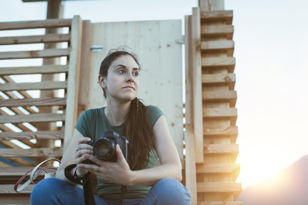 Pensive woman looking away and holding a professional digital camera, she is sitting outdoors Stock fotó