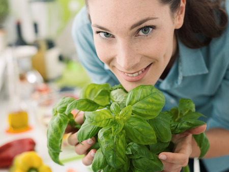 Smiling woman smelling fresh basil at home and preparing healthy food in the kitchen Archivio Fotografico