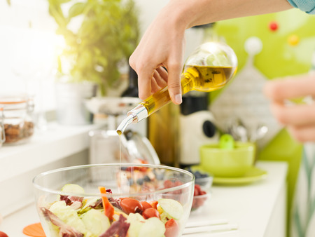 Woman preparing a fresh healthy vegan salad in her kitchen, she is seasoning vegetables with extra virgin olive oil, nutrition and diet concept