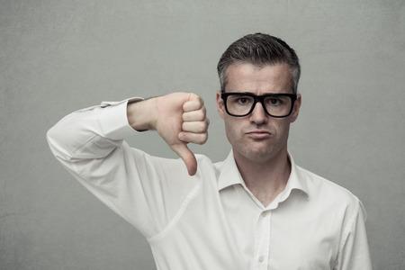 失望した男は親指を下にしてカメラを見て、嫌いと不承認の概念を見て