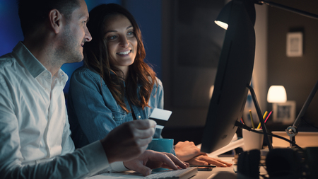 Happy smiling couple doing online shopping together, the man is holding a credit card Stock fotó