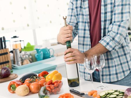Uomo che apre una bottiglia di vino bianco in cucina, sta usando un cavatappi Archivio Fotografico - 93146336