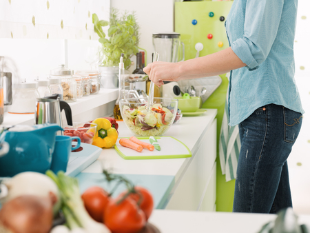 Woman preparing a fresh healthy vegan salad in her kitchen, she is mixing vegetables in the bowl, healthy food concept Standard-Bild - 93063086