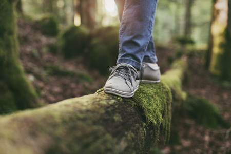 森の中の丸太の上を歩き、バランスをとる女性:運動、健康的なライフスタイル、調和の概念 写真素材