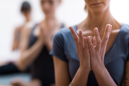Women practicing yoga and meditation together they are opening their clasped hands, healthy lifestyle and spirituality concept