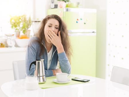 Femme paresseuse fatiguée prenant son petit déjeuner à la maison dans la cuisine, elle bâille et prend un café Banque d'images - 93007801