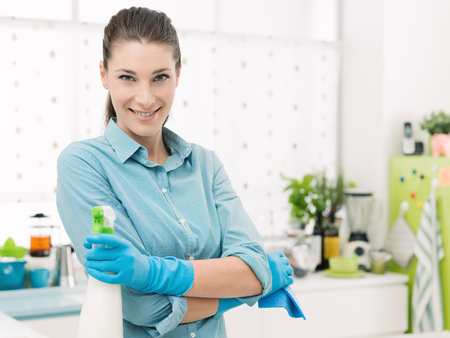 Smiling young housewife doing chores and using a spray detergent at home, she is posing with arms crossed in the kitchen Stock Photo
