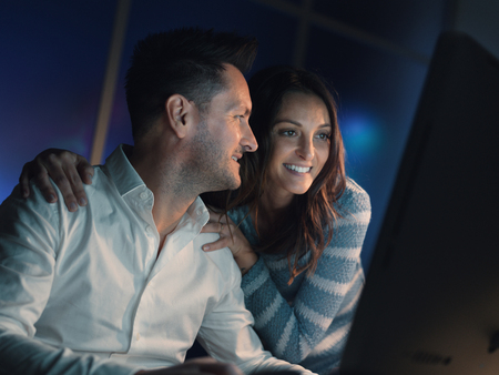 Happy couple relaxing at home late at night, they are connecting online and watching videos