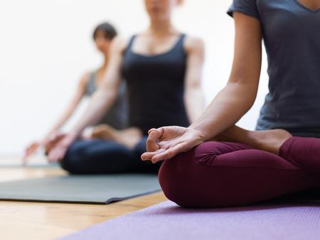 一緒にヨガを練習し、蓮のポーズに座っている女性:マインドフルネス瞑想、精神性と健康的なライフスタイルの概念