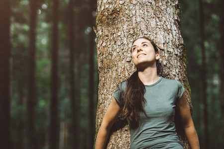 自然の中で微笑み、リラックスしている女性、彼女は木に寄りかかって、目をそらしています 写真素材