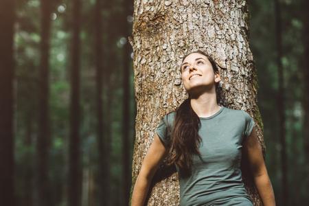 웃 고 자연 속에서 편안한 여자, 그녀는 나무에 기대어 멀리 찾고