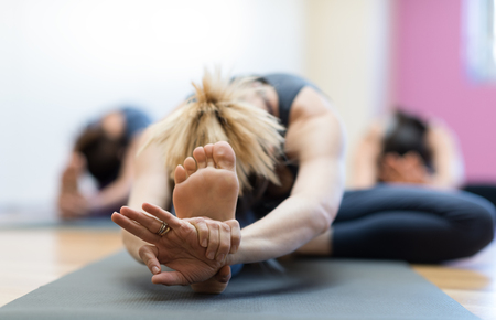 Woman doing physical exercise and stretching legs on a mat, foot close up, healthy lifestyle concept Imagens