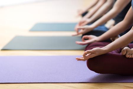 Frauen, die zusammen Yoga üben und im Lotos sitzen, werfen auf: Achtsamkeitsmeditation, Geistigkeit und gesundes Lebensstilkonzept