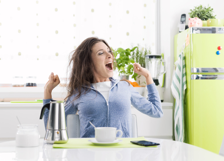 Tired lazy woman having breakfast at home in the kitchen, she is stretching and having a coffee Banco de Imagens