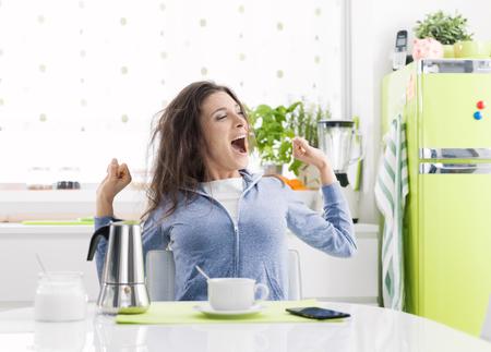 Vermoeide luie vrouw die ontbijt thuis in de keuken heeft, rekt zich uit en drinkt een koffie