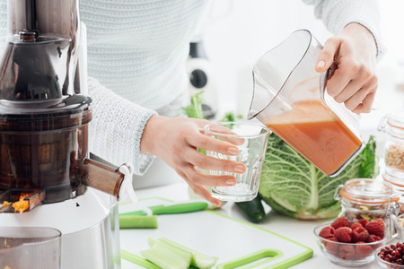 Woman pouring some fresh homemade juice in a glass, healthy food and fitness concept