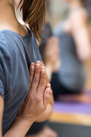 一緒にヨガを練習している若い女性は、逆の祈りのポーズを取り、背中の後ろで手を握っています 写真素材