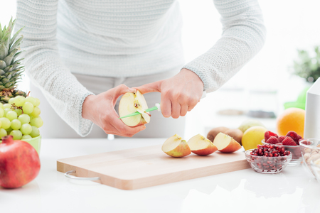 Die Frau, die einen gesunden strengen Snack des strengen Vegetariers in ihrer Küche vorbereitet, schneidet sie einen Apfel, die Hände, die oben schließen