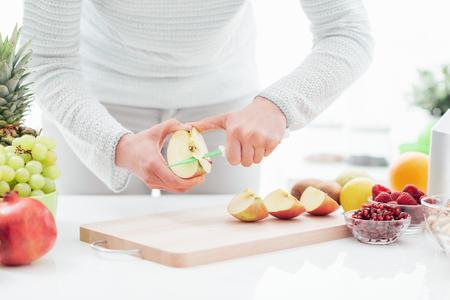 Kobieta przygotowuje zdrową wegańską przekąskę w swojej kuchni, kroi jabłko, ręce z bliska
