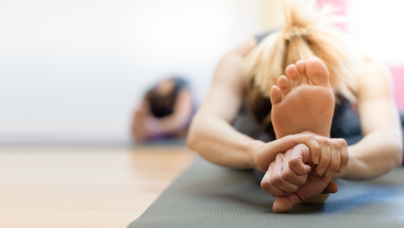 マットの上で運動やストレッチをする女性、足を閉じて、健康的なライフスタイルの概念 写真素材