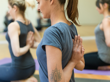 Young women practicing yoga together, they are doing the reverse prayer pose and clasping their hands behind their back Stock Photo