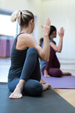 여자 체육관에서 함께 요가 연습, 그들은 매트에 척추 트위스트 위치하고있다