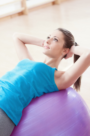 Attractive young woman working out with fitness ball in the gym, pilates exercise.
