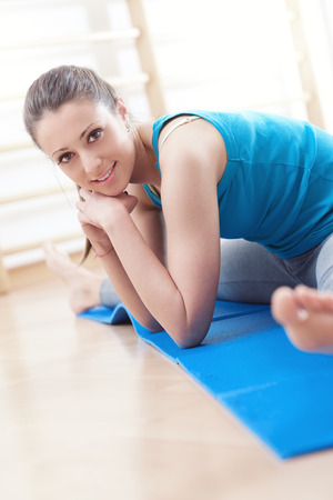 Attractive woman working out at gym doing stretching exercises on a mat for legs.
