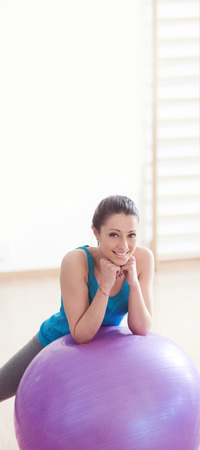 Smiling young woman working out at gym with fitness physioball.