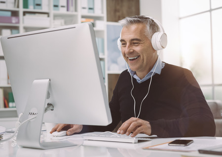 행복한 사람이 헤드폰을 착용하고 그의 집 사무실에서 온라인으로 영화를보고, 그는 즐기고 웃는 스톡 콘텐츠