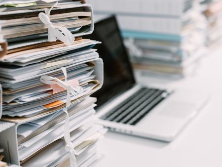 piles de paperasse dans le bureau et ordinateur portable sur le bureau Banque d'images