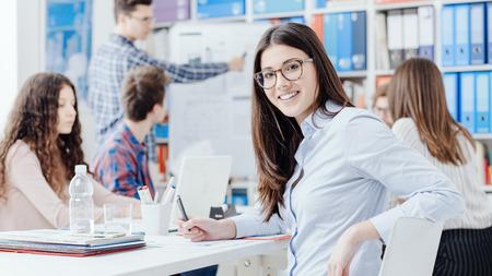 Joven equipo de negocios reunidos en la oficina y sonriente mujer confiada posando, puesta en marcha y lluvia de ideas concepto