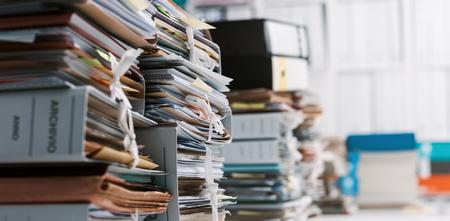 Pile di scartoffie e file in ufficio: sovraccarico di lavoro, gestione dei file e concetto di amministrazione