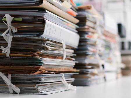 Stapel Papierkram und Akten im Büro: Arbeitsüberlastung, Aktenmanagement und Verwaltungskonzept